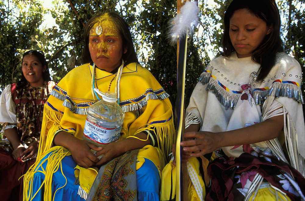 After six hours of continuous dancing at a Sunrise Dance, an Apache girl's first menstruation rite, the girl rests in camp together with her helper and a cousin on the San Carlos Apache Indian Reservation in Arizona, USA. The girl is covered with sacred yellow pollen from the cattail plant, which has been applied as a blessing by the medicine man and the relatives. The Sunrise Dance is an enactment of the Apache creation myth and during the rites the girl 'becomes' Changing Woman, a mythical female figure, and comes into possession of her healing powers. The rites are also supposed to prepare the girl for adulthood and to give her a long and healthy life without material wants.