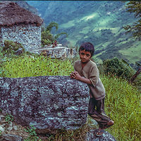 A youngster rests beside millet fierlds surrounding his family's hut ner Gandrung, Nepal.