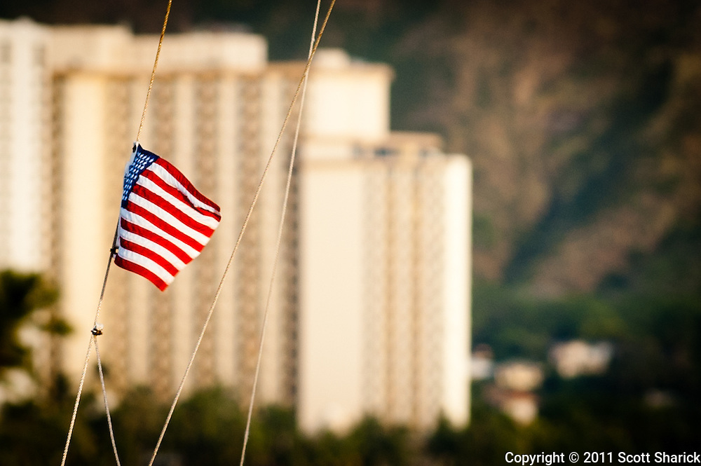 A flag on a sailboat waves in the wind in Waikiki.