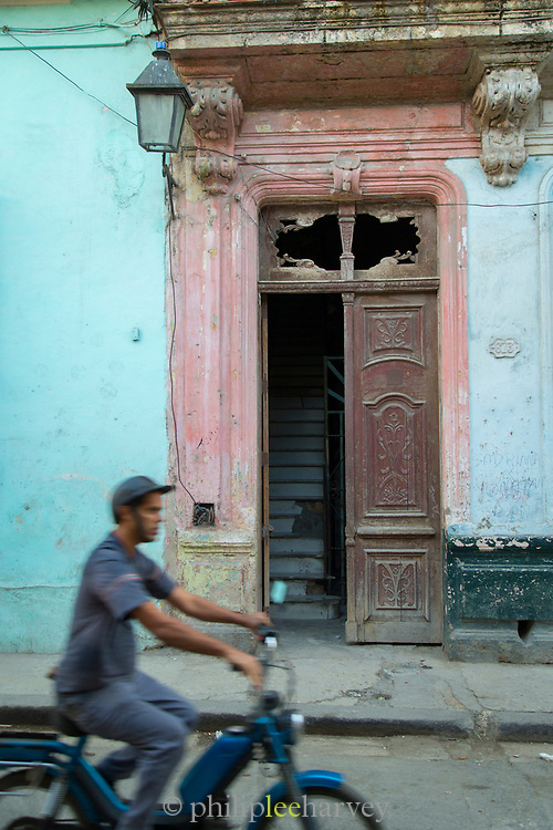 Man riding motorcycle on old town street, Havana, Cuba