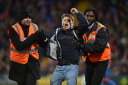 a Sunderland fan is taken away by stewards after running onto the pitch after Jermain Defoe of Sunderland scores his teams 1st goal to make it 0-1. Barclays Premier league match, Crystal Palace v Sunderland at Selhurst Park in London on Monday 23rd November 2015.<br /> pic by John Patrick Fletcher, Andrew Orchard sports photography.