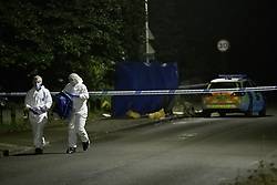 © Licensed to London News Pictures. 08/10/2021. Oxford, UK. Forensic investigators walk away from the crime scene in Bayswater Road, Barton in Oxfordshire. Police were called just before 6:00pm today, Friday 08/10/2021, to reports of a man being stabbed, the victim, a man aged in his thirties, died of his injuries at the scene. Photo credit: Peter Manning/LNP