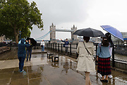 Tourists with umbrellas taking photographs in front of Tower Bridge during rain and wet weather in London, England on August 10, 2018