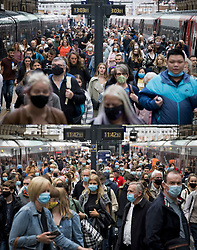 © Licensed to London News Pictures. 31/07/2021. London, UK. Comparison picture showing passengers disembarking a train at Kings Cross, with many not wearing face masks, today 31/07/2021 (TOP), and the same scene taken on 10/07/2021 with all passengers wearing masks (BOTTOM). The UK's COVID-19 cases continue to fall following the removal of restrictions on July 19th. Photo credit: Ben Cawthra/LNP