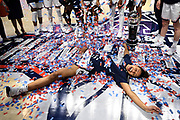 Connecticut's Olivia Nelson-Ododa makes an angel in confetti at the end of an NCAA college basketball game against Cincinnati in the American Athletic Conference tournament finals at Mohegan Sun Arena, Monday, March 9, 2020, in Uncasville, Conn. (AP Photo/Jessica Hill)