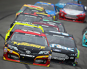 Clint Bowyer (15) and Carl Edwards (99) lead other racers as they make their way around the track during a NASCAR Sprint Cup Series race at Kansas Speedway, Sunday, April 21, 2013 in Kansas City, Kansas. (AP Photo/Colin E. Braley)