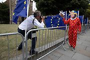 Anti Brexit protester dressed up as a clown version of Prime Minister Boris Johnson is photographed by a press photographer outside parliament in Westminster as it is announced that Boris Johnson has had his request to suspend Parliament approved by the Queen on 28th August 2019 in London, England, United Kingdom. The announcement of a suspension of Parliament for approximately five weeks ahead of Brexit has enraged Remain supporters who suggest this is a sinister plan to stop the debate concerning a potential No Deal.