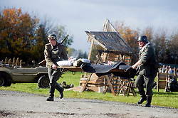 Pickering 1940s war weekend Northern World war Two Association battle reenactment. Reenactors, one portraying a Field Policeman, the other a German Soldier evacuate casualties by stretcher as a forward aid post comes under threat from an allied attack. October 2009 Image Copyright Paul David Drabble