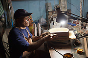 A Cuban potter in his studio working under a lamp, making ceramic bowls, Havana.