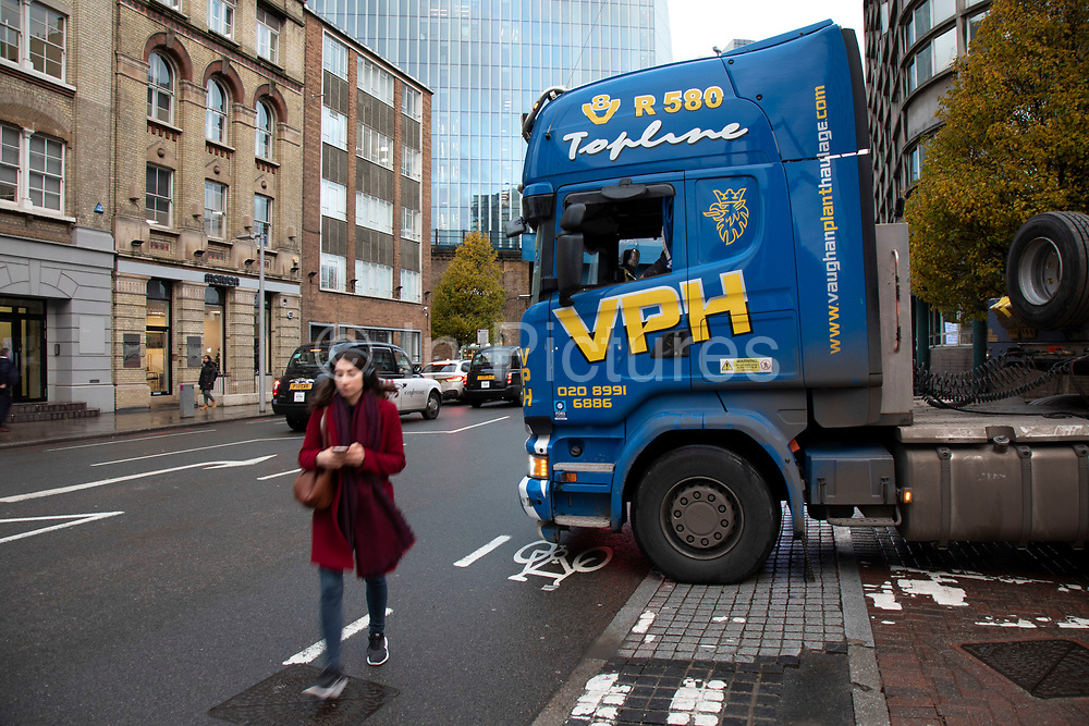 Woman walks into the road around the cab of a large heavy goods vehicle turning right onto Southwark Street on 27th November 2019 in London, England, United Kingdom. A great deal of construction in the capital means that the roads are often full of heavy good vehicles, which is a road safety concern for many other road users.