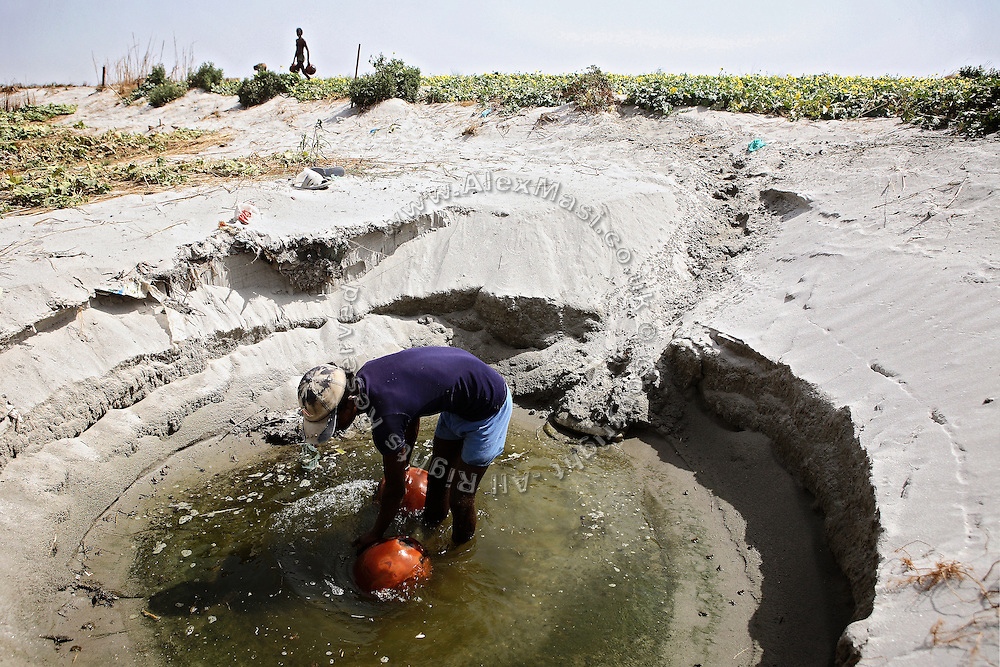 Agricultural labourers are collecting water devoted to irrigation from pools forming on the side of the polluted Ganges River in Kanpur, Uttar Pradesh, near Jajmao Industrial Area. Sustaining life for thousands of years along the Indo-Gangetic plains, the river's ecosystem is in grave danger of being damaged beyond repair while crops absorb the contaminants from the water and pass it on to those consuming the vegetables grown in this area.