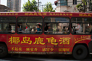 People on a public transport bus covered in Chinese characters in Shanghai, China.
