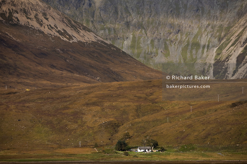 Lone remote crofter's farmhouse sits isolated beneath the 2,542 foot Glamaig mountain in dramatic landscape at Moll, Isle of Skye, Scotland.