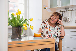 Happy senior woman having tea at a dining table in kitchen, Munich, Bavaria, Germany