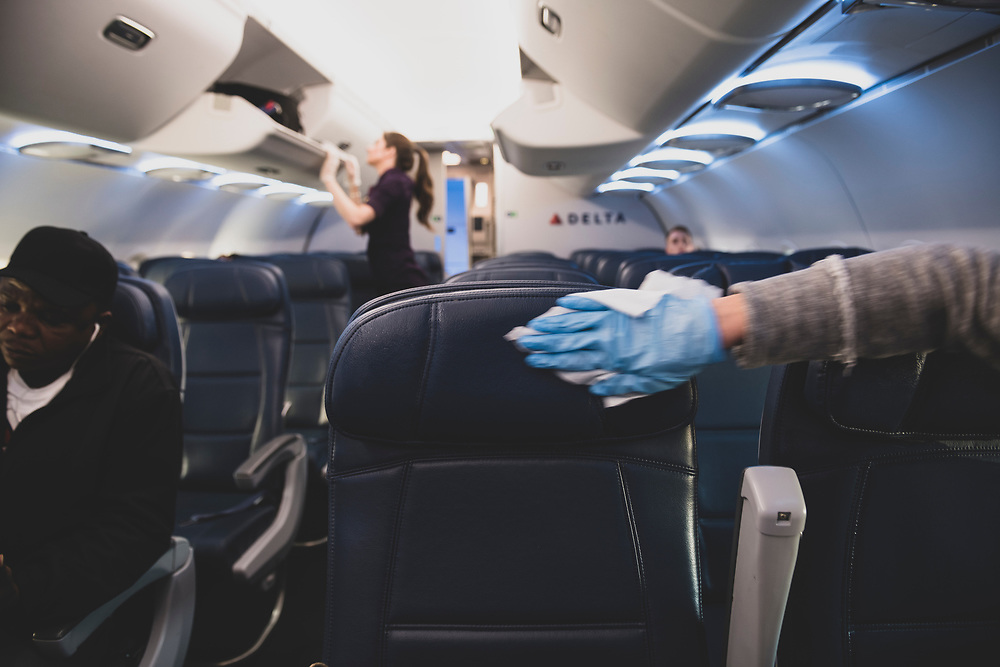 On a Delta flight from New York's Laguardia Airport to Atlanta, a passenger who has just boarded  wears a plastic glove while using a wipe to disinfect the airplane seats and armrests on her row. (March 21, 2020)