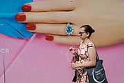 A lady carries a wire coat hanger while passing a temporary construction hoarding for the jewellery retailer Hirsch that features a manicured hand, painted nails and an unheated Paraíba Tourmaline ring, set with fine white diamonds designed by HIRSH, on 13th August 2019, in London England.