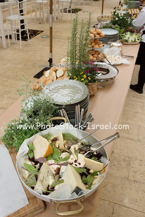 An assortment of foods in bowls on a buffet table during a evening event