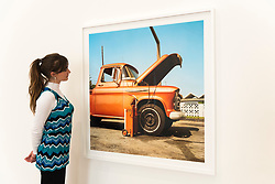 "© Licensed to London News Pictures. 10/04/2019. LONDON, UK. A staff member views a work by American photographer William Eggleston at his new exhibition ""2¼"" at the David Zwirner gallery in Mayfair.  The show comprises a series of square-format colour photographs taken around 1977 throughout California and the American South and will run April 12 to June 1, 2019. Photo credit: Stephen Chung/LNP"