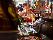 """07 AUGUST 2014 - BANGKOK, THAILAND:  A woman prays at an alter at Pek Leng Keng Mangkorn Khiew Shrine. Thousands of people lined up for food distribution at the Pek Leng Keng Mangkorn Khiew Shrine in the Khlong Toei section of Bangkok Thursday. Khlong Toei is one of the poorest sections of Bangkok. The seventh month of the Chinese Lunar calendar is called """"Ghost Month"""" during which ghosts and spirits, including those of the deceased ancestors, come out from the lower realm. It is common for Chinese people to make merit during the month by burning """"hell money"""" and presenting food to the ghosts. At Chinese temples in Thailand, it is also customary to give food to the poorer people in the community.     PHOTO BY JACK KURTZ"""