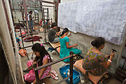 Nepalese adult workers of the R.C Rug Factory in the Narayanthan area of Kathmandu, Nepal. They weave carpets and rugs using a loom. The R.C Rug Factory export to Europe, U.S and Canada; and rely on the Good Weave certificate of approval to boast excellent quality and fair conditions for its workers. This is because the carpet factory industry in Nepal is notorious for providing poor working conditions and forcing young children into labour.