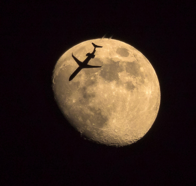 A plane is crossing over the Moon.