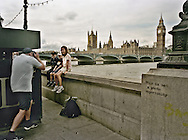A father photographs his children at a spot near the London Eye and the Parliament building.  August 2003.