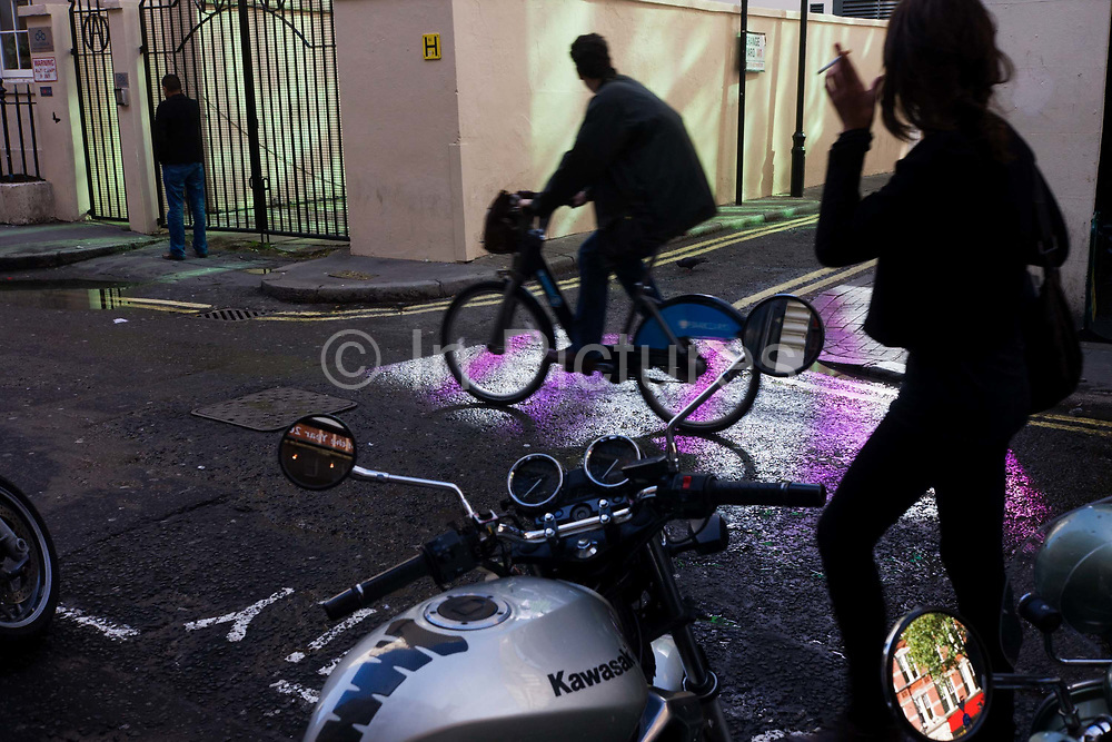 """Pedestrian and cyclist on rental Boris Bike in a Soho side-street, patterned with purple. During a bust lunchtime in London's Soho many pedestrians and cyclists pass-by a splash of purple that plays across a side street off Charing Cross Road. Produced by reflective coloured panels on an adjacent building - and after a period of light rain in the capital, the vivid rays of colour are a welcome oasis of hues. Motorcycles are parked with mirrors showing the street beyond. A lady walks across the landscape with a cigarette in hand and a male cyclist pedals past on a """"Boris bike"""" - one of the rental bicycles that can be hired for 30-minute journeys across the capital."""