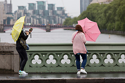 © Licensed to London News Pictures. 14/05/2015. London, UK. Two women struggle to control their umbrellas during heavy rain and wet and windy weather in Westminster, central London today. Photo credit : Vickie Flores/LNP