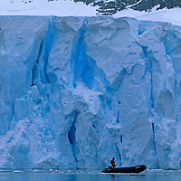 A zodiac driver from a cruise ships takes a few quiet moments below the calving face of a coastal glacier on the Antarctic Peninsula, Antarctica.