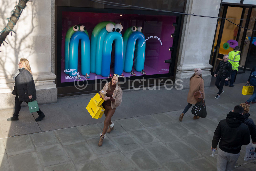 Carrying three yellow branded shopping bags, a lady emerges the Selfridges department store on Londons Oxford Street, and passes by a themed window display that includes some cartoon-esque characters wishing the public a happy new decade, on 7th February 2020, in London, England.