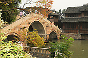 China, Zhejiang Province, Wuzhen a two-thousand-year village proud of it's ancient stone bridges floating on mild water, its stone pathways between the mottled walls and its delicate wood carvings. Ancient bridge