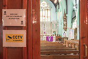 A sign on a wall stating live streaming in operation while Father Matthew Uche Ndibe delivers mass to parishioners via live-stream at on 27th March 2020 at St Peters Roman Catholic Church in Woolwich, London, United Kingdom. Following the governments advice on social distancing, the Catholic Church has suspended public worship until further notice to help slow the spread of the Coronavirus. Designed by Augustus Pugin in 1841-42 in the style of the Gothic Revival, St Peters RC,  is one of only three Pugin churches in London. In 1883 St Peter the Apostle Roman Catholic Church opened, the first to do so in London, following the Reformation.