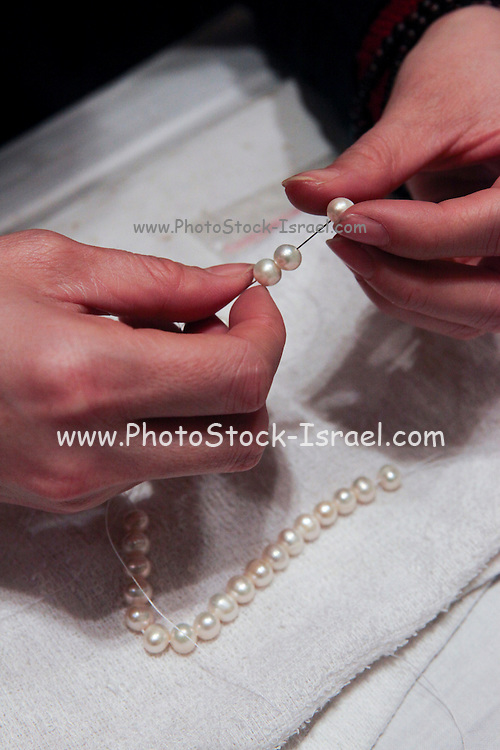 China, Beijing, woman working in a pearl factory showroom Stringing pearls