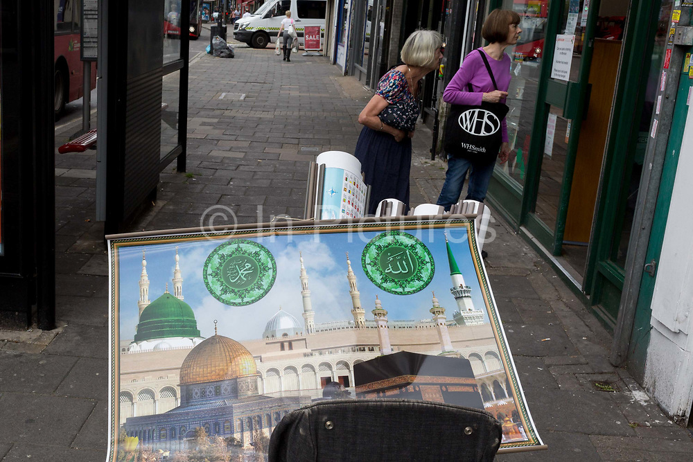 Two women window shop in front of an Islamic image of Mecca, one of many in a trolley full of posters that a man is offering for sale to local businesses along the Walworth Road in Southwark, south London on 22nd August 2019, in London, England.