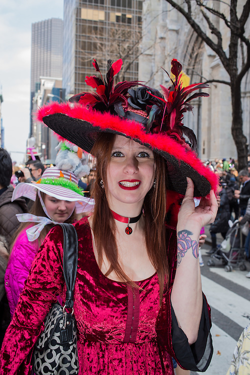 New York, NY, USA-27 March 2016. A woman in a red velvet dress wears a black and red hat in the annual Easter Bonnet Parade and Festival.