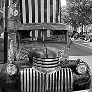 A vintage 1941 truck with American flag back-drop.
