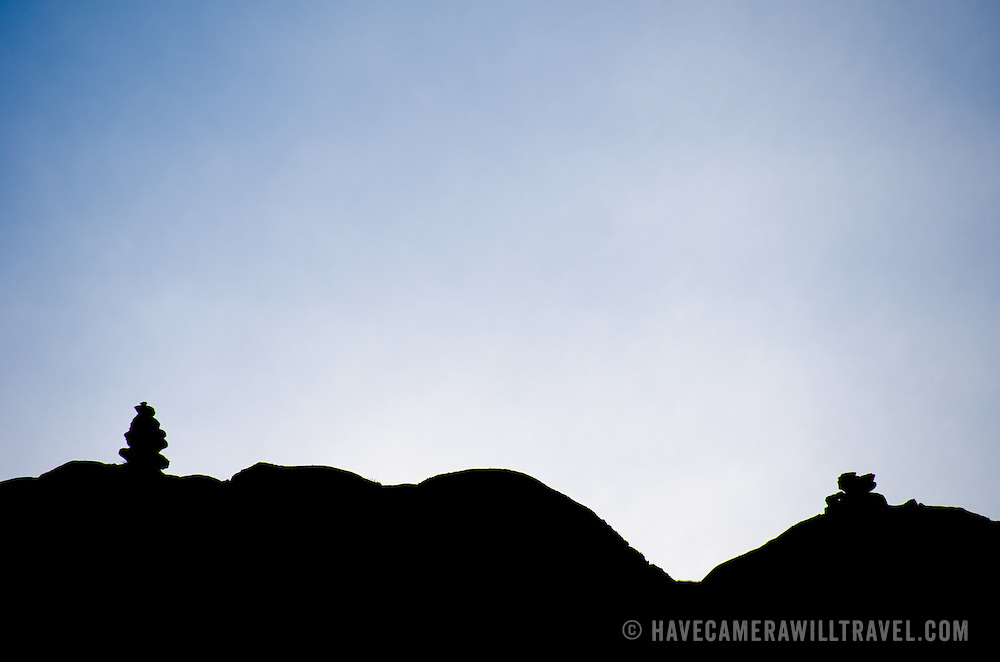 Two small stone cairns mark the way and are silhouetted Moir Hut Camp (13,660 feet) on Mt Kilimanjaro's Lemosho Route.