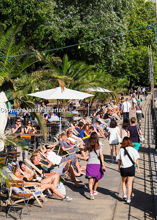 Busy cafe and bar beside Spree River in MonbijouPark Mitte Berlin
