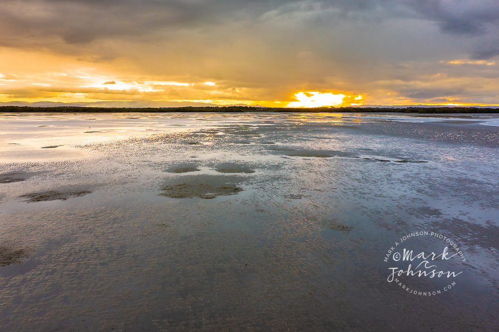 Mudflats reflect the setting sun at low tide, Moreton Bay, Queensland, Australia
