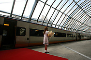 An unidentified girl waits with a bouquet of flowers on a deserted station platform for Britain's Queen Elizabeth to arrive at Waterloo station in London on 11 July 2007 to board a Eurostar train to Brusslels, as she prepares for her visit to Belgium. AFP PHOTO/CHRIS YOUNG