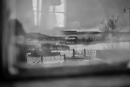 A working croft seen in the reflection of a broken shed window in Ardmair Bay, Scotland.