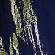 A Real Journey's tourist cruise ship dwarfed by the steep cliff faces of Milford Sound, South Island, New Zealand. .Milford Sound (Piopiotahi in Ma¯ori) is a fjord in the south west of New Zealand's South Island, within Fiordland National Park and the Te Wahipounamu World Heritage site. It has been judged the world's top travel destination and is acclaimed as New Zealand's most famous tourist destination..Milford Sound runs 15 kilometres inland from the Tasman Sea at Dale Point - the mouth of the fiord - and is surrounded by sheer rock faces that rise 1,200metres (3,900ft) or more on either side. Among the peaks are The Elephant at 1,517metres (4,977ft), said to resemble an elephant's head and The Lion, 1,302metres (4,272ft), in the shape of a crouching lion. Lush rain forests cling precariously to these cliffs, while seals, penguins, and dolphins frequent the waters and whales can be seen sometimes..Milford Sound sports two permanent waterfalls all year round, Lady Bowen Falls and Stirling Falls. After heavy rain many hundreds of temporary waterfalls can be seen running down the steep sided rock faces. .The beauty of this landscape draws thousands of visitors each day, with between 550,000 and 1 million visitors in total per year. This makes the sound one of New Zealand's most-visited tourist spots, and also the most famous New Zealand tourist destination.  Milford Sound, New Zealand. 29th April 2011. Photo Tim Clayton