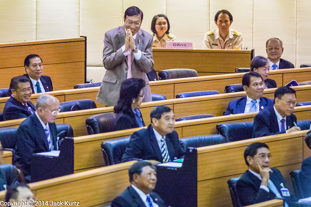 08 AUGUST 2014 - BANGKOK, THAILAND: Newly elected President of the National Legislative Assembly (NLA) PORNPETCH WICHITCHOLCHAI stands to thank members of the NLA after he was unanimously elected Friday. The Thai National Legislative Assembly (NLA) met Friday at the Parlimanet Building in Bangkok to elect legislative leadership. The NLA was appointed by the Thai junta, formally called the National Council for Peace and Order (NCPO), and is supposed to guide Thailand back to civilian rule after a military coup overthrew the elected government in May. There are 197 members of the NLA. Membership is tilted towards military personnel. From the Royal Thai Army 40 members are Generals, 21 are Lt. Generals and 7 are Major Generals. From the Royal Thai Air Force 17 are Air Chief Marshals and 2 are Air Marshals. From the Royal Thai Navy, 14 are Admirals and 5 are Vice Admirals. There are also 6 Police Generals and 3 Police Lt. Generals. There are 187 men in the NLA and only 10 women.        PHOTO BY JACK KURTZ