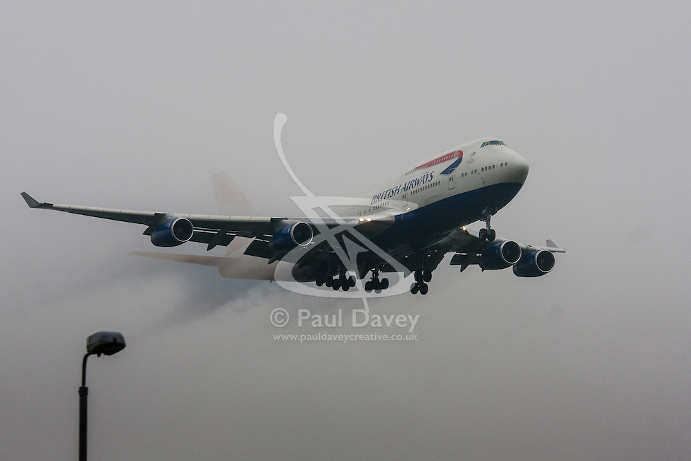 """January 3rd 2015, Heathrow Airport, London. Low cloud and rain provide ideal conditions to observe wake vortexes and """"fluffing"""" as moisture condenses over the wings of landing aircraft. With the runway visible only at the last minute, several planes had to perform a """"go-round"""", abandoning their first attempts to land. PICTURED: Water vapour streaming from its wings, a British Airways Boeing 747 Jumbo Jet emerges from the low cloud moments before touchdown on Heathrow's runway 27L."""