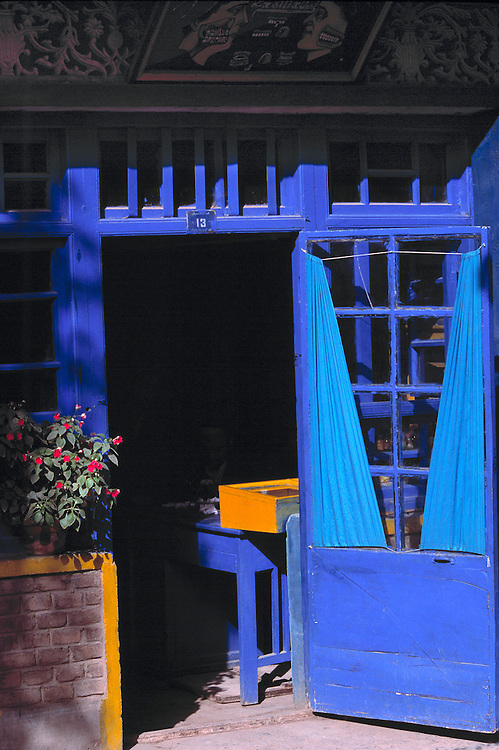 Behind an open, periwinkle blue-painted door with blue curtains, an orange box is visible in Kashgar, Xinjiang, China.