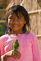 Kuna Indian girl holding a parakeet in her village on Corbisky Island, San Blas Islands (Kuna Yala), Caribbean Sea, Panama