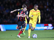 AFC Bournemouth midfielder Dan Gosling, Liverpool striker Raheem Sterling during the Capital One Cup match between Bournemouth and Liverpool at the Goldsands Stadium, Bournemouth, England on 17 December 2014.