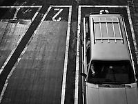 a monochrome image of the parking lanes and one vehicle viewed from above showing lanes and numerals 1 and 2 aboard a Washington state ferry in Puget Sound, WA, USA
