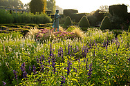 The Lamp of Wisdom statue in the formal garden surrounded by Salvia, Sedum, ornamental grasses and Yew topiary at Waterperry Gardens, Waterperry, Wheatley, Oxfordshire