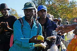 JOHANNESBURG, SOUTH AFRICA - APRIL 12: Homeless, unemployed and families living below the bread line, gather in Mayfair to meet Shareef and his team who handed out a total of 300 food parcels on April 12, 2020 in Johannesburg South Africa. Under pressure from a global pandemic. President Ramaphosa declared a 21 day national lockdown extended by another two weeks, mobilising goverment structures accross the nation to combat the rapidly spreading COVID-19 virus - the lockdown requires businesses to close and the public to stay at home during this period, unless part of approved essential services. (Photo by Dino Lloyd)